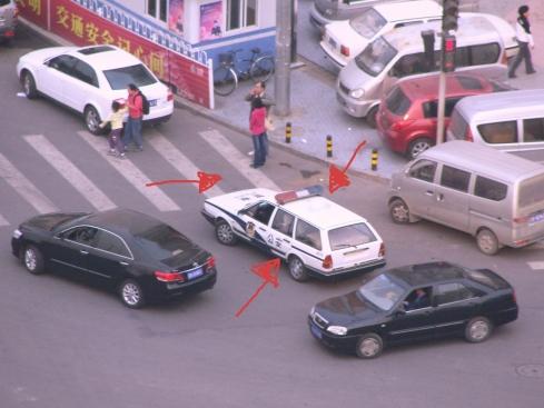 Carro de la policía estacionado de forma estratégica en un cruce y frente al rayado peatonal